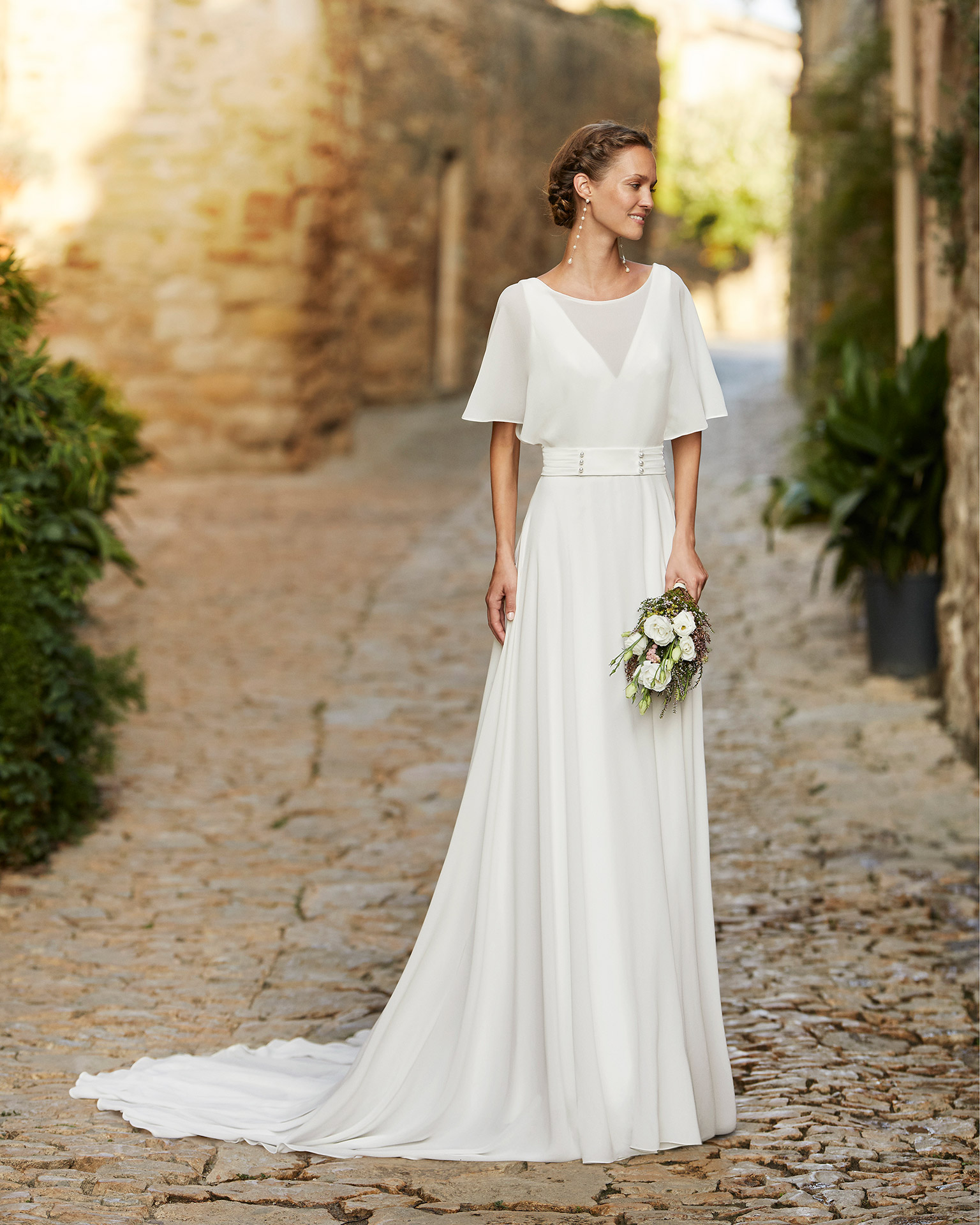 Boho-chic ballgown-style wedding dress and transparent yoke; with a plunging neckline and an open back with long draped crespon. Delicate Alma Novia model in crepe. 2022 ALMANOVIA Collection.