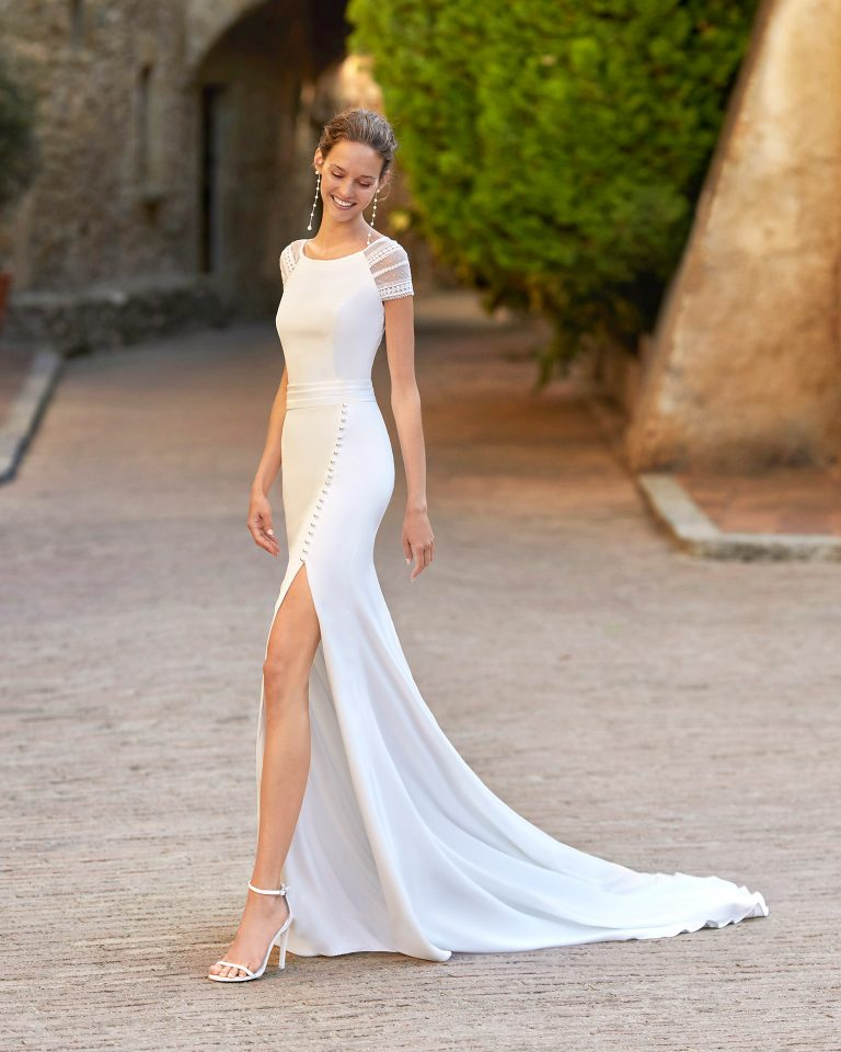 Boho-chic sheath-style wedding dress with side slit in skirt; with a bateau neckline and closed back and sleeves with dot tulle. Alma Novia model in crepe. 2022 ALMANOVIA Collection.