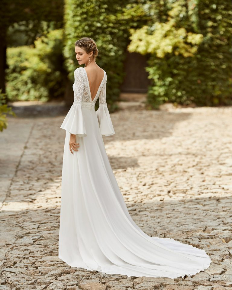 Boho-chic ballgown-style wedding dress with a lace bodice; with a bateau neckline and V-back with bell sleeves. Alma Novia model in crespon. 2022 ALMANOVIA Collection.
