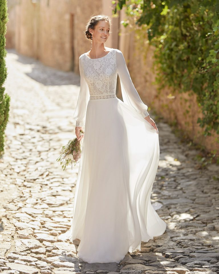 Boho-chic sheath-style wedding dress with a lace bodice and detachable train; with a bateau neckline and V-back with long bulging sleeves. Delicate Alma Novia model in georgette. 2022 ALMANOVIA Collection.