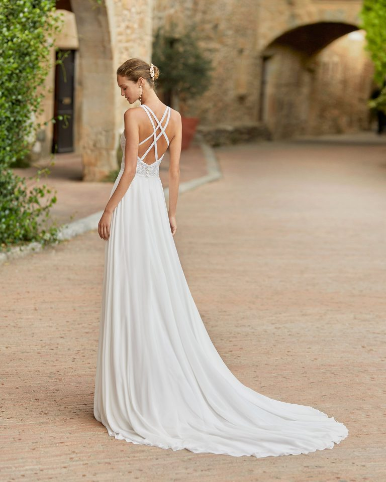 Boho-chic ballgown-style wedding dress with a lace bodice; with a round neckline and back with crossed shoulder straps. Alma Novia model in georgette. 2022 ALMANOVIA Collection.