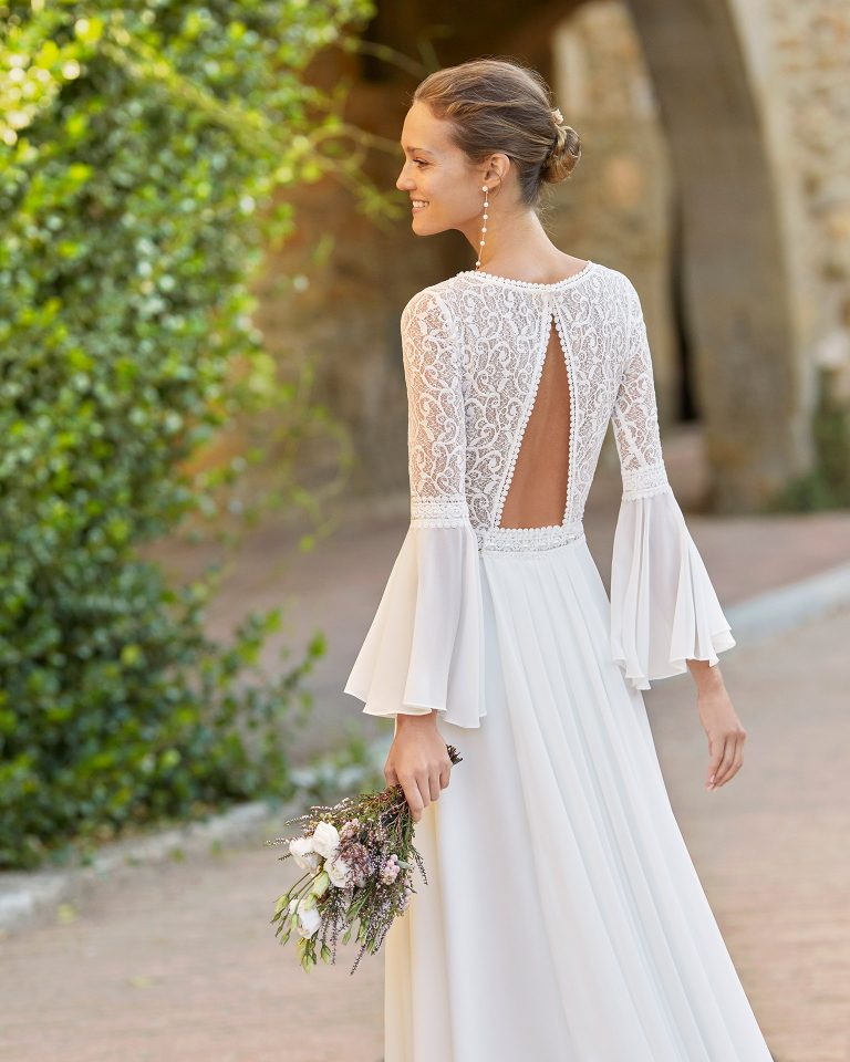 Boho-chic sheath-style wedding dress with a lace bodice and detachable train; With a V-neckline and triangular back with three-quarter flounced sleeves. Alma Novia model in georgette. 2022 ALMANOVIA Collection.