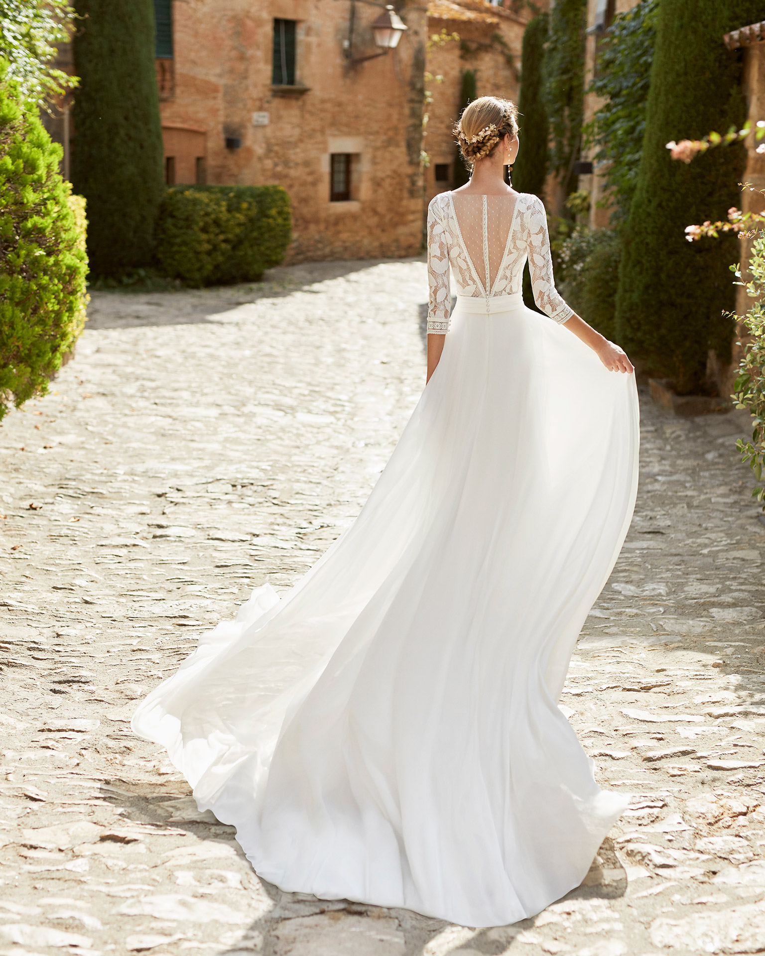 Romantic ballgown-style wedding dress with a lace bodice; with a V-neckline, a closed back with dot tulle and pearl buttons, and three-quarter sleeves with lace on the cuffs. Unique Alma Novia model in georgette. 2022 ALMANOVIA Collection.