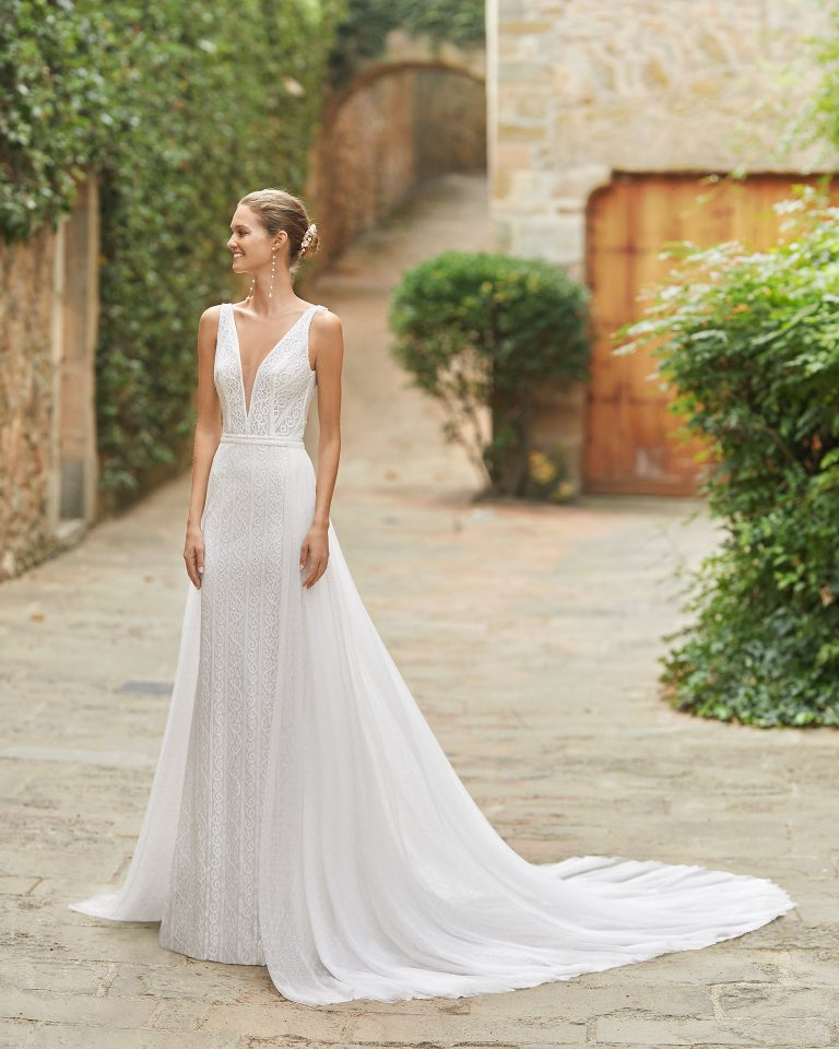 Simple sheath-style wedding dress with a detachable dot tulle overskirt; with a V-neckline, open back, beadwork details at the waist and neckline. Alma Novia model in lace. 2022 ALMANOVIA Collection.
