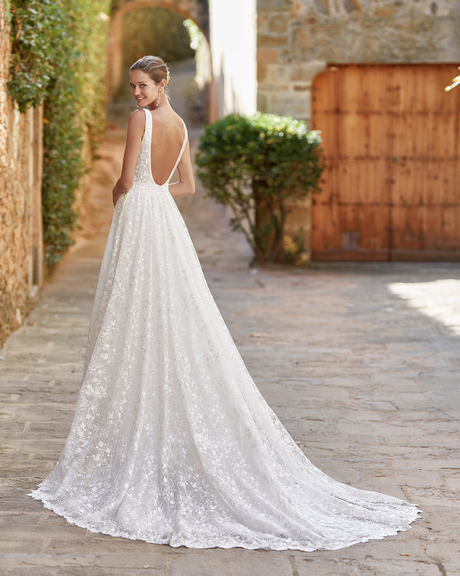 Romantic ballgown-style wedding dress; with a V-neckline, open back, beadwork details at the neckline and sleeves. Unique Alma Novia model in lace. 2022 ALMANOVIA Collection.