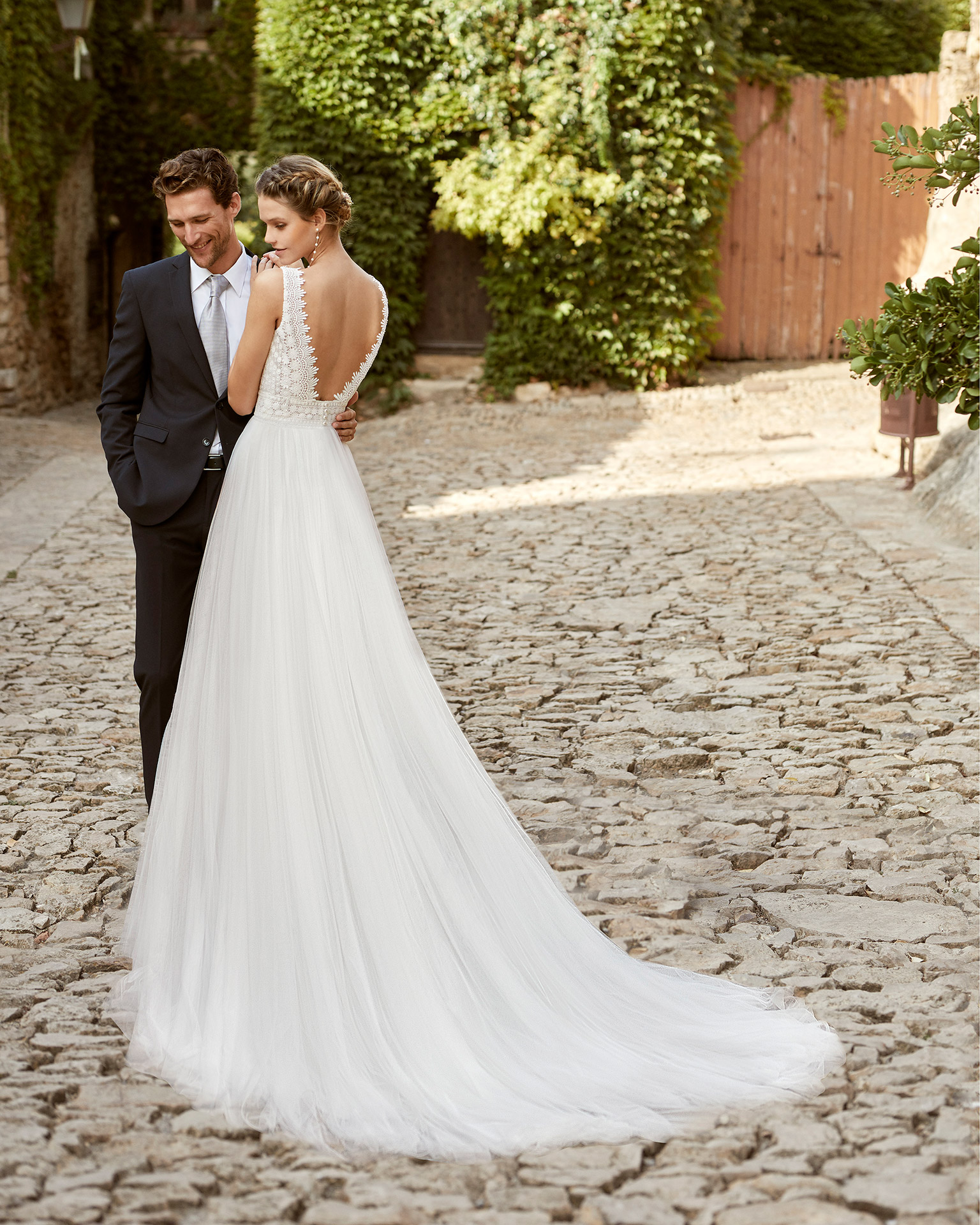 Romantic ballgown-style wedding dress with a lace bodice; a V-neckline, open back and lightweight skirt with soft tulle and lace edging applied to the skirt. Alma Novia model in tulle and lace. 2022 ALMANOVIA Collection.