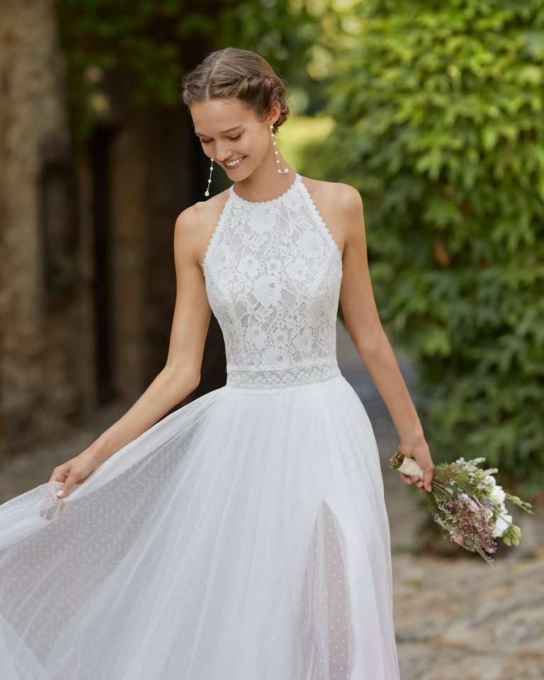 Lightweight sheath-style wedding dress with a lace bodice and slit in skirt; with a halter neck, closed back with lace and pearl buttons, and beadwork details at the waist. Alma Novia model in dot tulle. 2022 ALMANOVIA Collection.