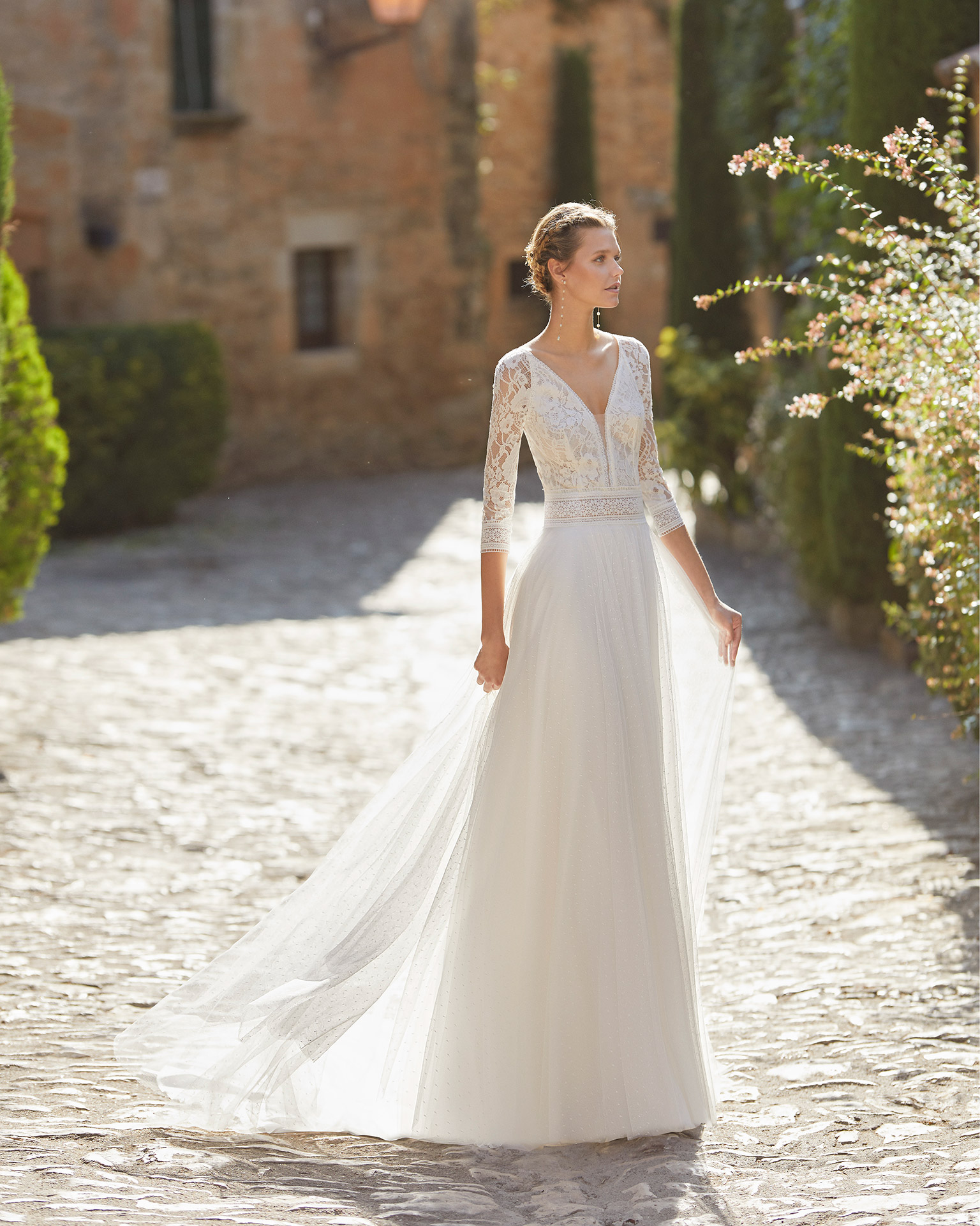 Delicate sheath-style wedding dress with a lace bodice; with a V-neckline, a closed back with lace and pearl buttons, and three-quarter sleeves. A dreamlike Alma Novia model in dot tulle. 2022 ALMANOVIA Collection.
