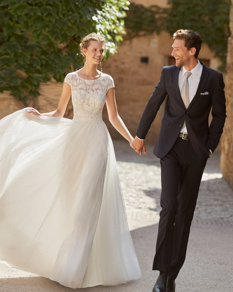 Romantic sheath-style wedding dress with a lace bodice; bateau neckline, a closed back with dot tulle, pearl buttons and short sleeves. Alma Novia model in dot tulle. 2022 ALMANOVIA Collection.