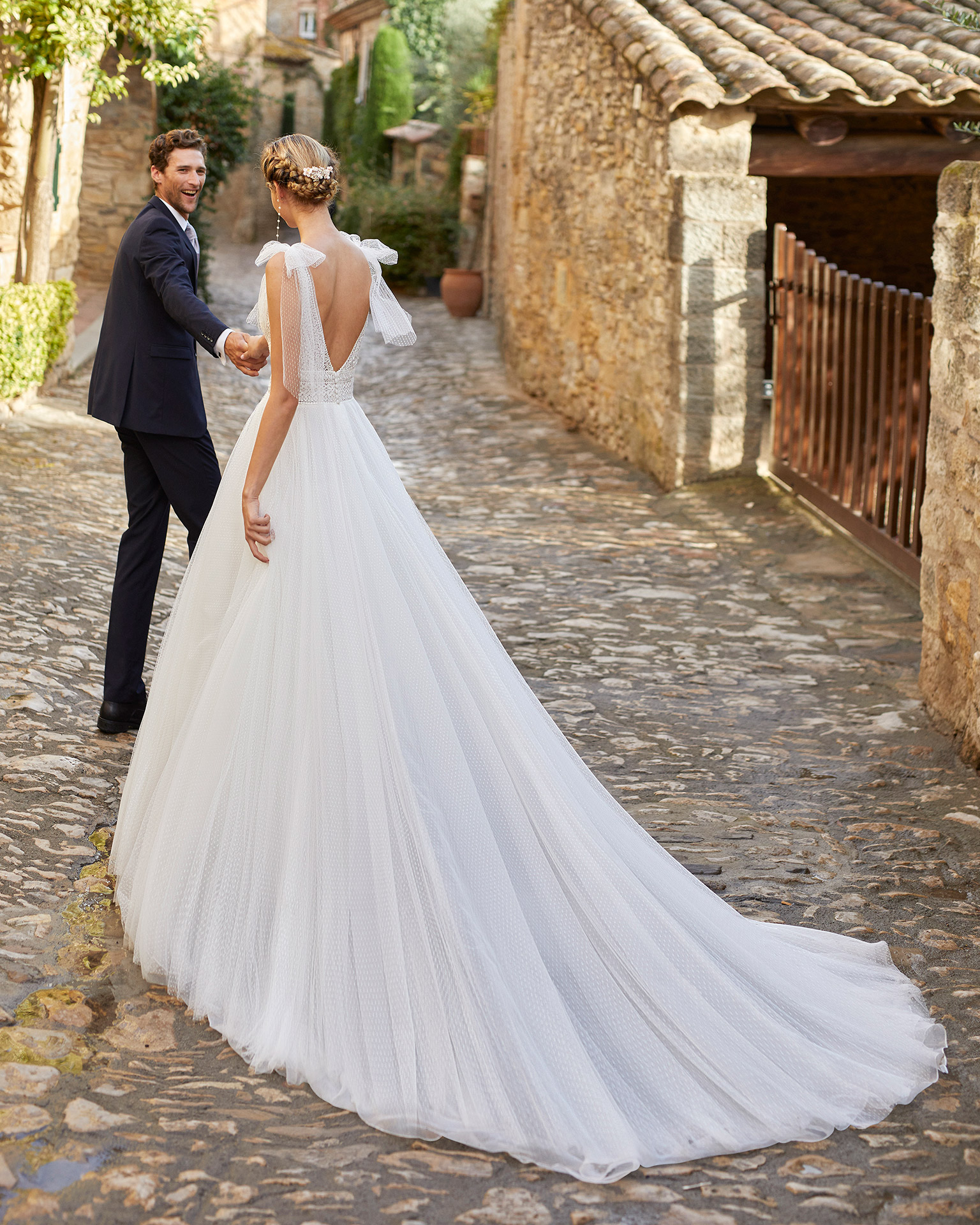 Romantic princess wedding dress with a lace bodice with slight draped dot tulle. V-neckline and plunging back. Alma Novia model in dot tulle. 2022 ALMANOVIA Collection.