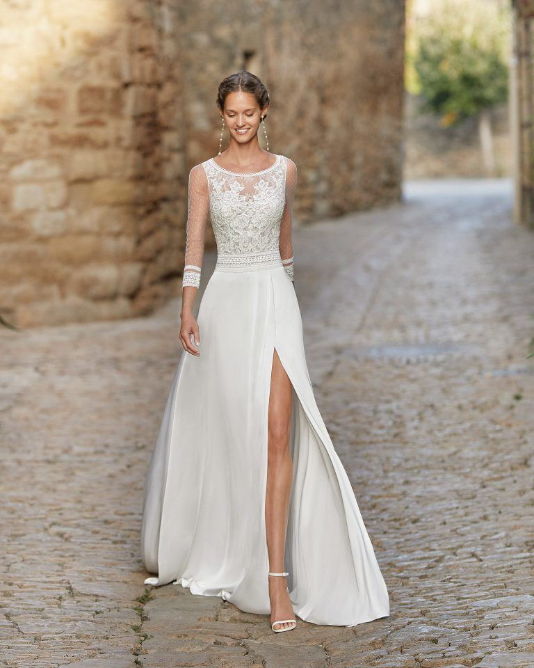 Boho-chic sheath-style wedding dress with a lace bodice and side slit in skirt; with a round neck, teardrop back and three-quarter sleeves. Unique Alma Novia model in crepe. 2022 ALMANOVIA Collection.