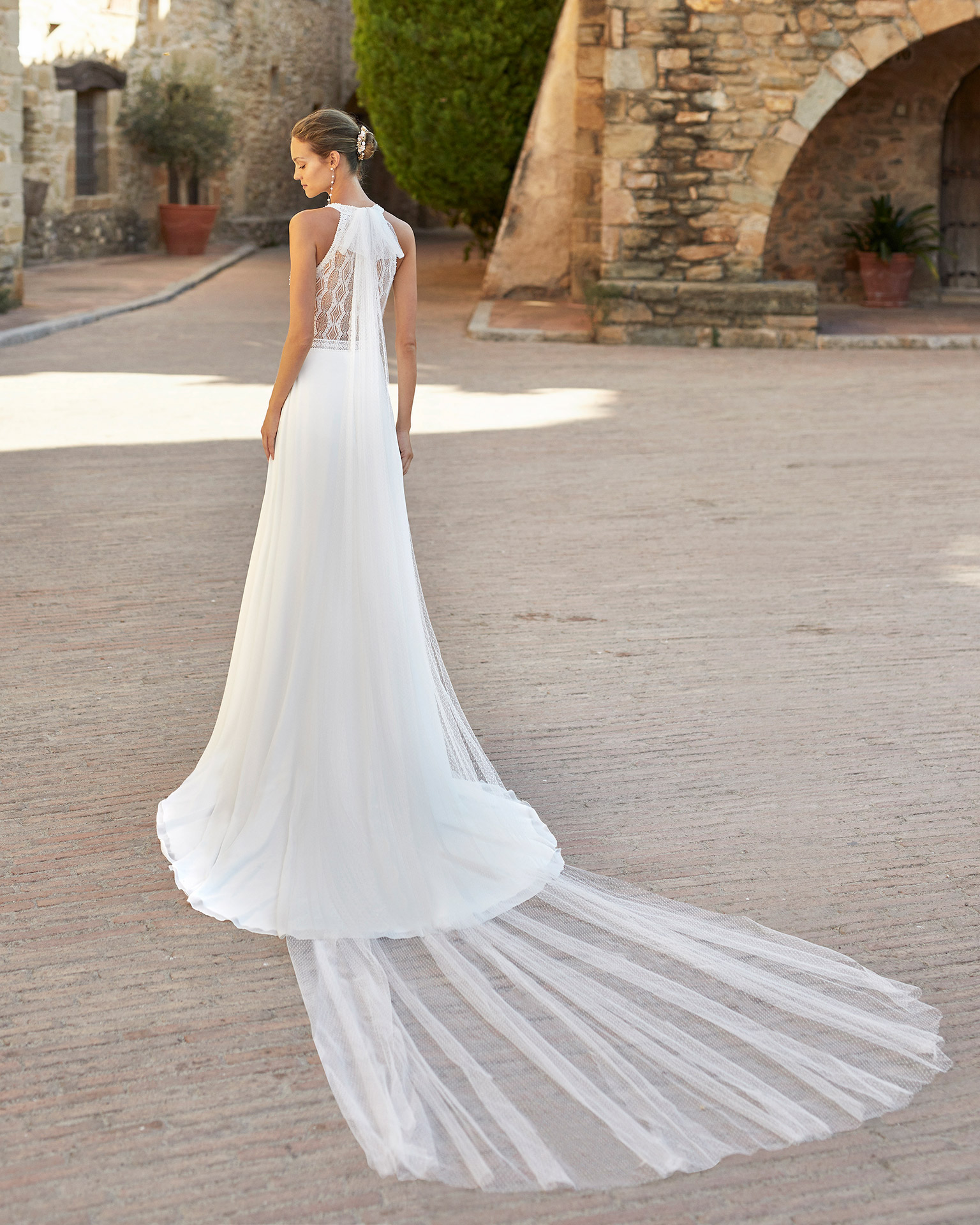 Boho-chic sheath-style wedding dress with a beadwork lace bodice and side slit in skirt; with a halter neck and long draped tulle from the neck. Alma Novia model in georgette. 2022 ALMANOVIA Collection.