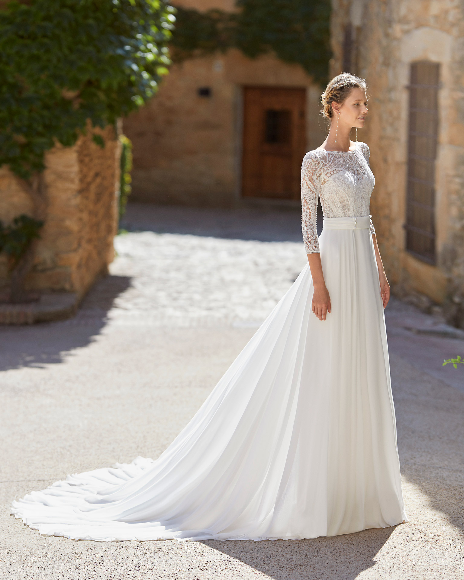 Boho-chic ballgown-style wedding dress with a lace bodice; with a bateau neckline, open back and three-quarter sleeves. Alma Novia model in georgette. 2022 ALMANOVIA Collection.