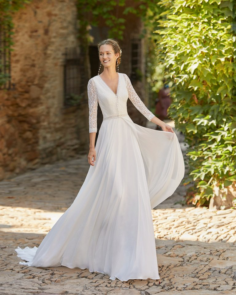 Boho-chic ballgown-style wedding dress with a long lace bridal coat; deep-plunge V-neckline and plunging back. Delicate Alma Novia model in georgette. 2022 ALMANOVIA Collection.