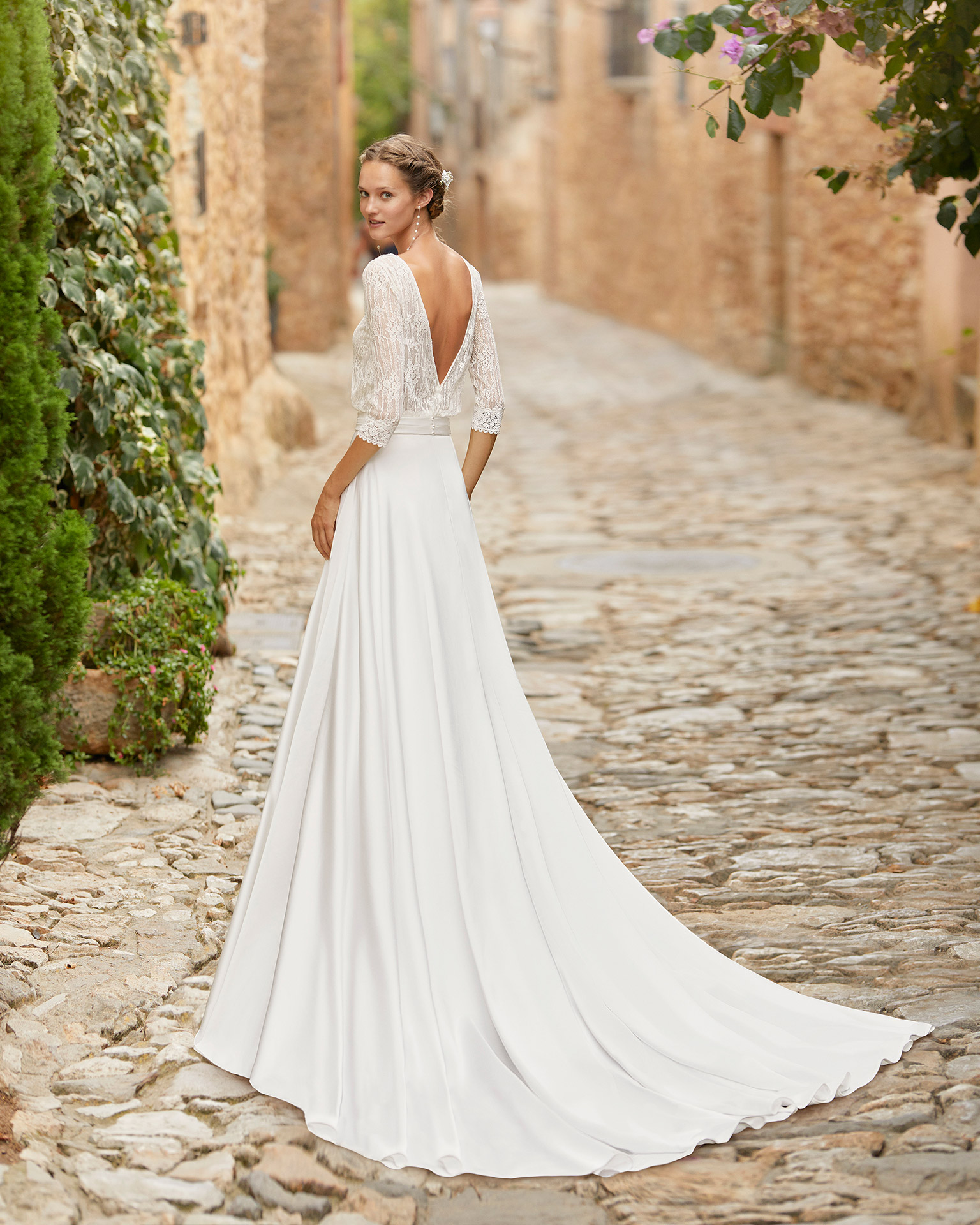 Boho-chic ballgown-style wedding dress with a lace bodice; with a bateau neckline and V-back with three-quarter sleeves; Unique Alma Novia model in crepe. 2022 ALMANOVIA Collection.