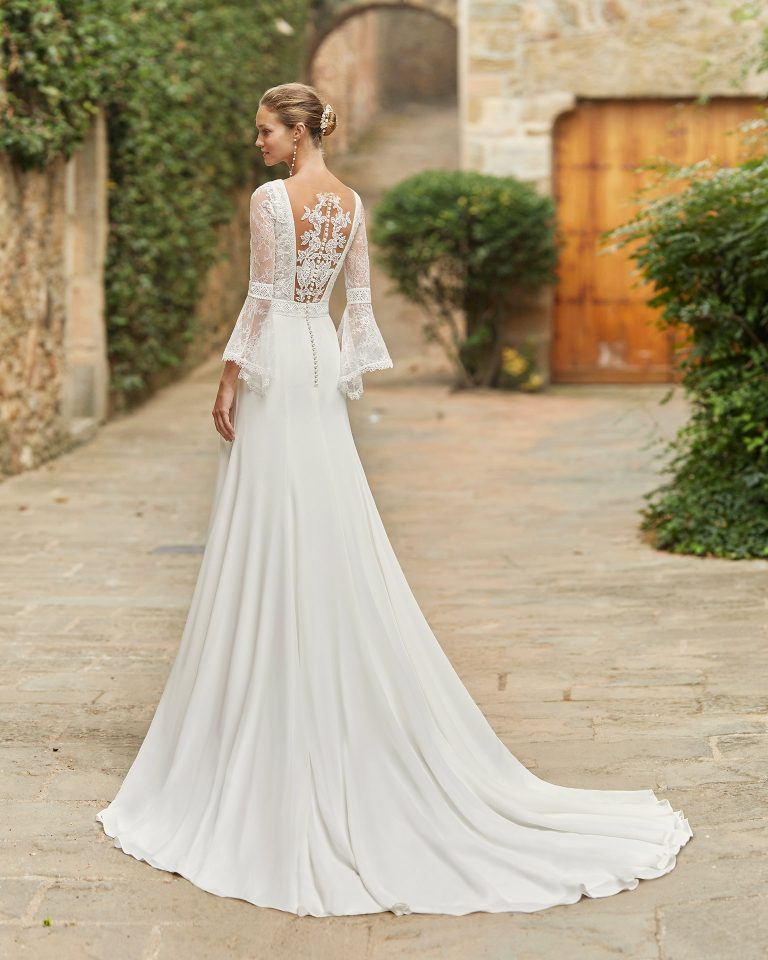 Boho-chic ballgown-style wedding dress with a lace bodice; with a V-neckline and tattoo-effect back with three-quarter flounced sleeves. Alma Novia model in georgette. 2022 ALMANOVIA Collection.