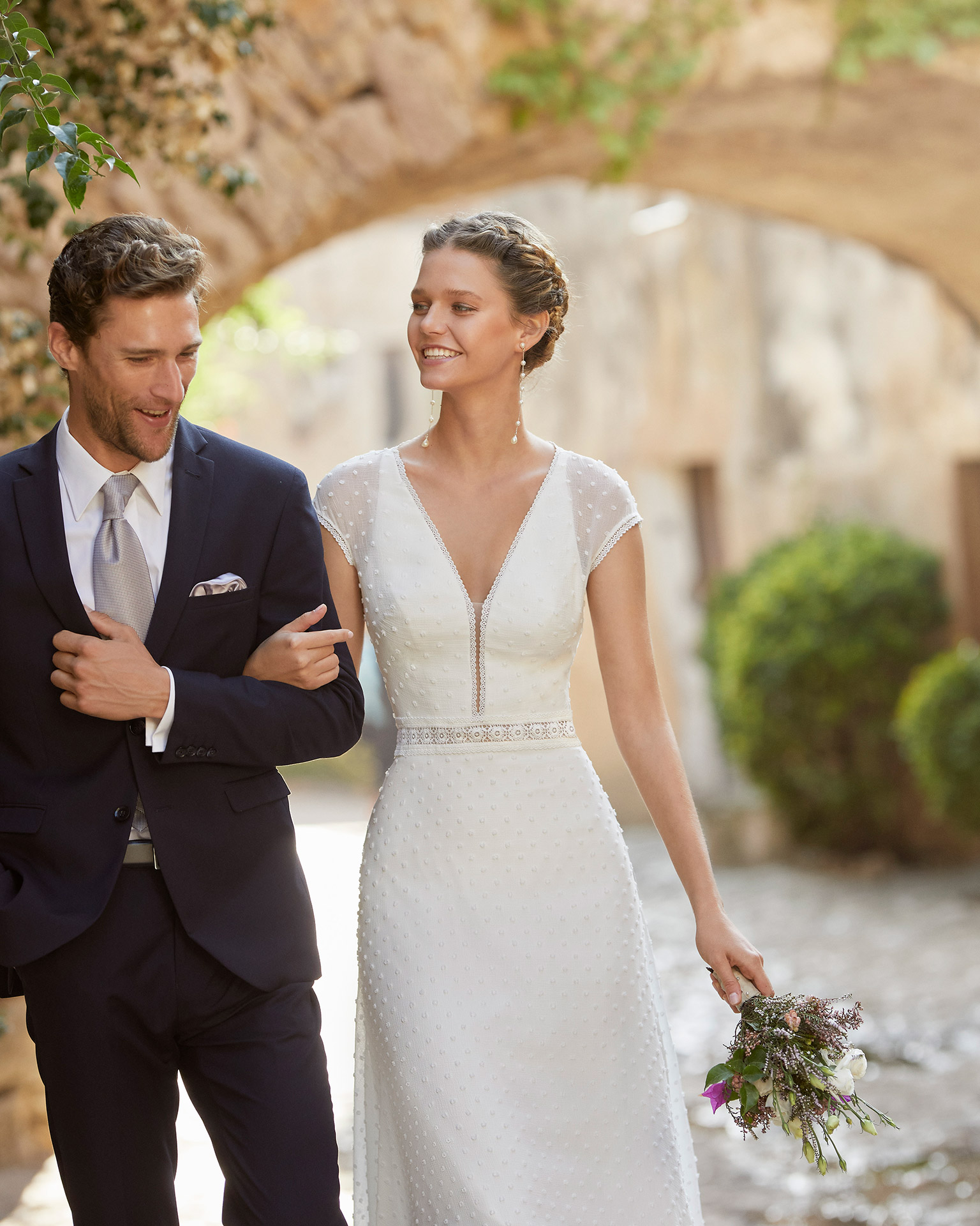 Boho-chic sheath-style wedding dress; with V-neckline, closed back and raglan sleeves. Unique Alma Novia model in polka-dot chiffon. 2022 ALMANOVIA Collection.