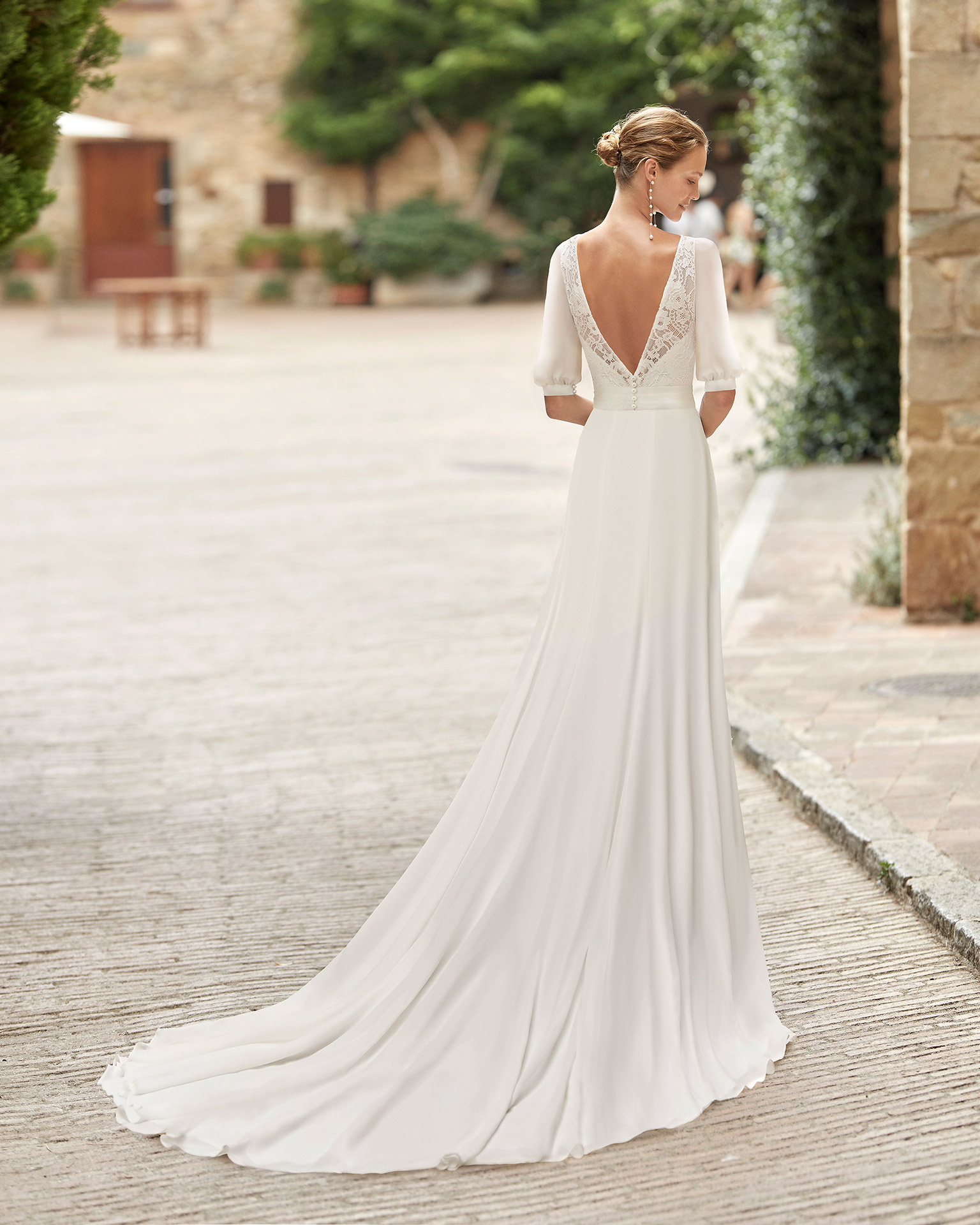 Boho-chic sheath-style wedding dress with a lace bodice; with a bateau neckline and V-back with three-quarter sleeves. Delicate Alma Novia model in georgette. 2022 ALMANOVIA Collection.