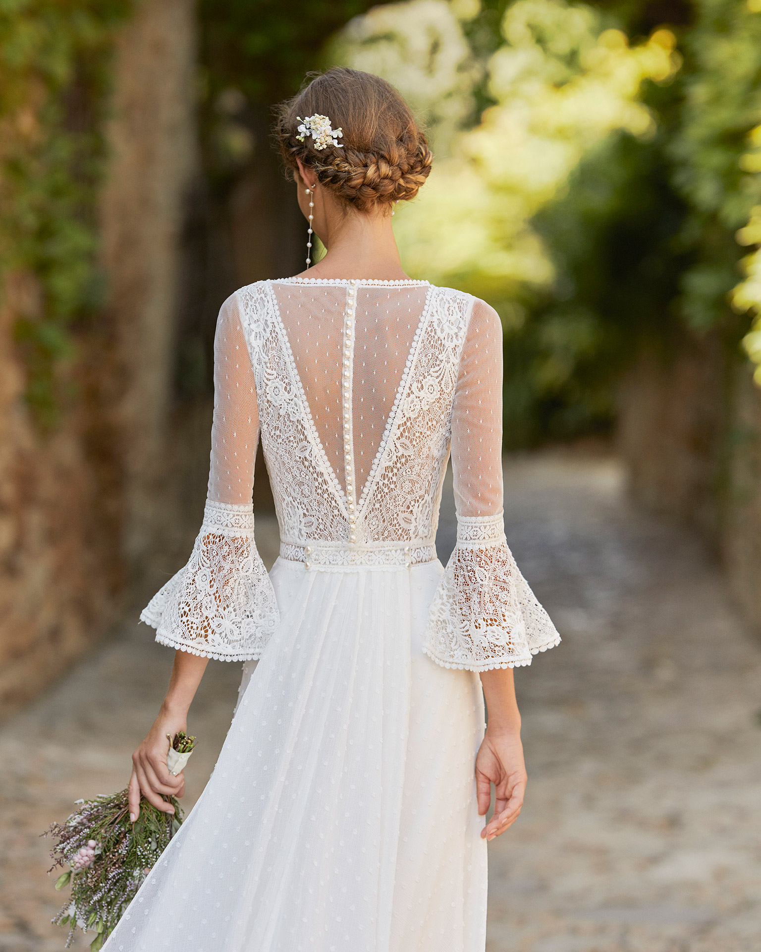 Boho-chic ballgown-style wedding dress with a lace bodice and detachable train; With a V-neckline, a closed back with dot tulle and pearl buttons, and three-quarter sleeves with a lace flounce. Alma Novia model in polka-dot chiffon. 2022 ALMANOVIA Collection.