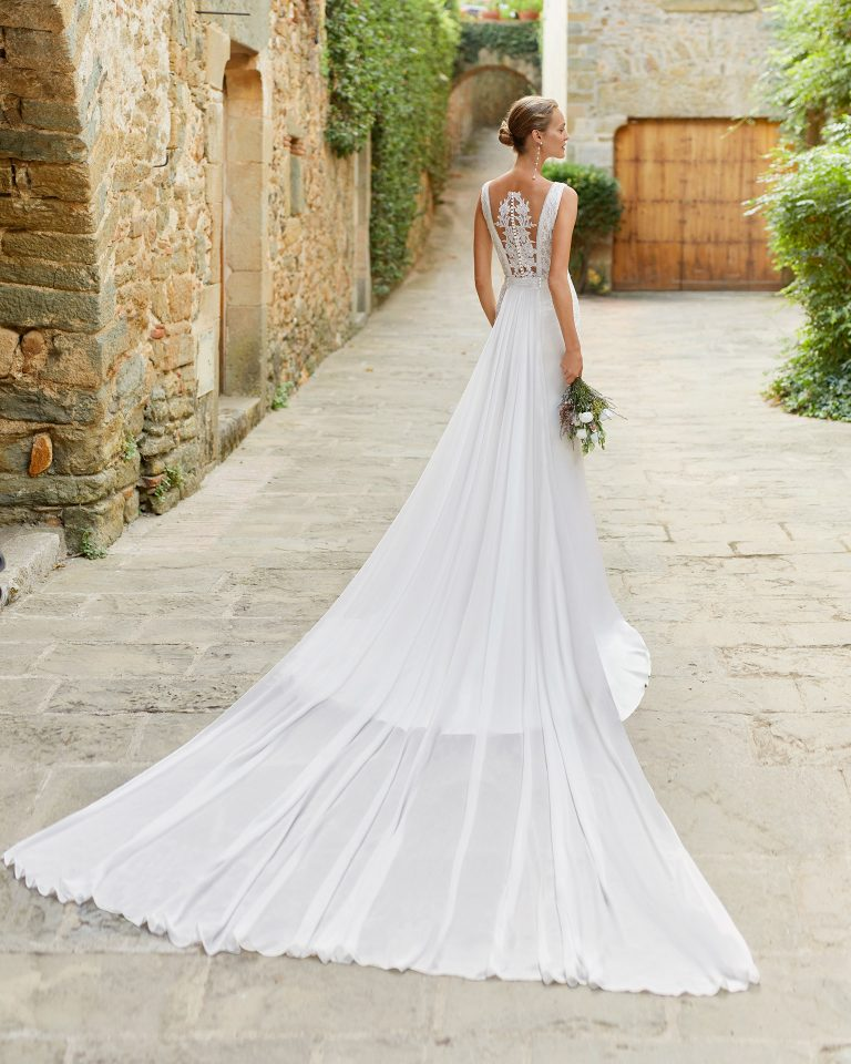 Boho-chic mermaid-style wedding dress with a lace bodice and detachable train; With V-neckline and tattoo-effect back. Alma Novia model in crepe. 2022 ALMANOVIA Collection.