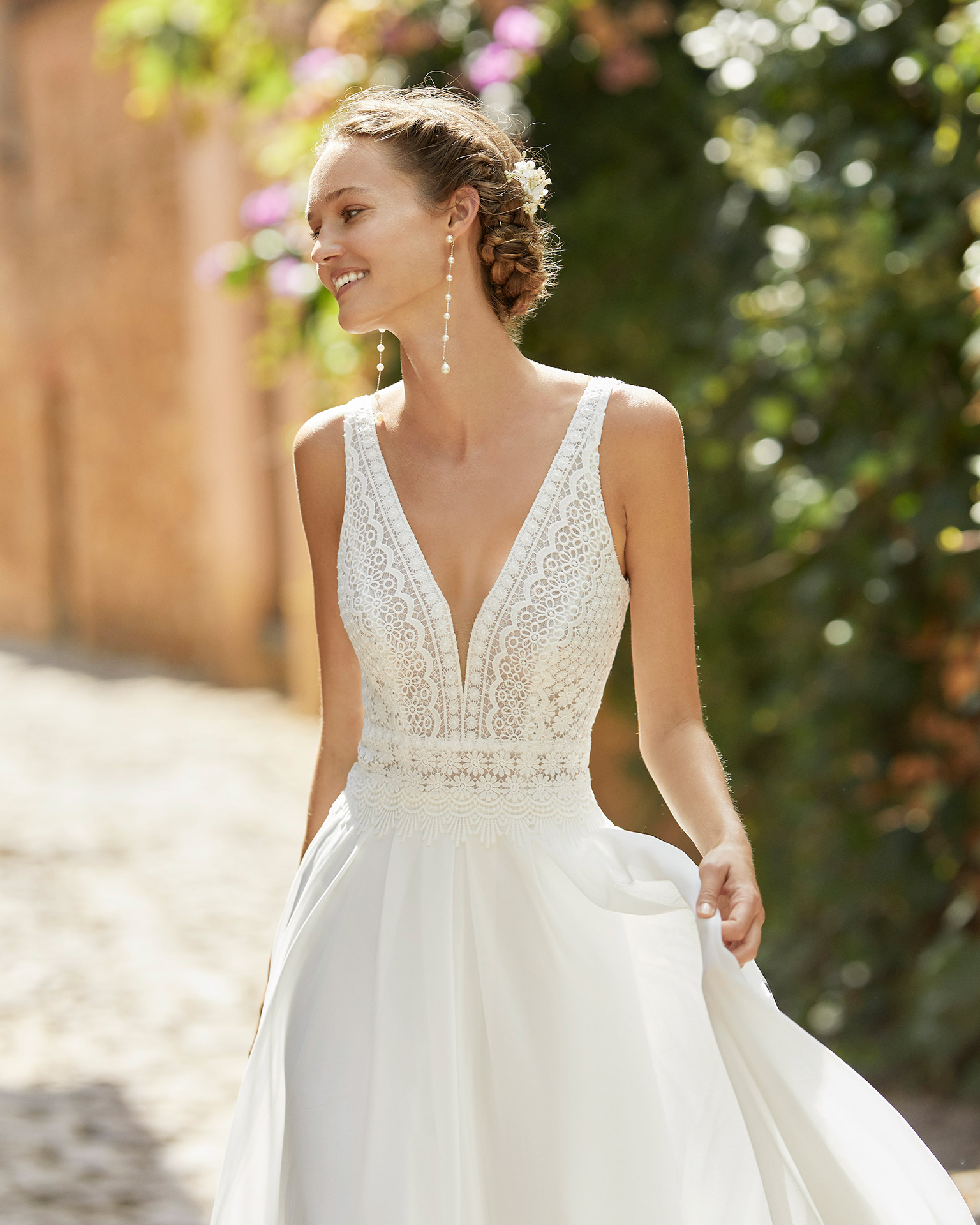 Delicate ballgown-style wedding dress with a lace bodice; with a V-neck, square back and pleated skirt. Unique Alma Novia model in georgette. 2022 ALMANOVIA Collection.