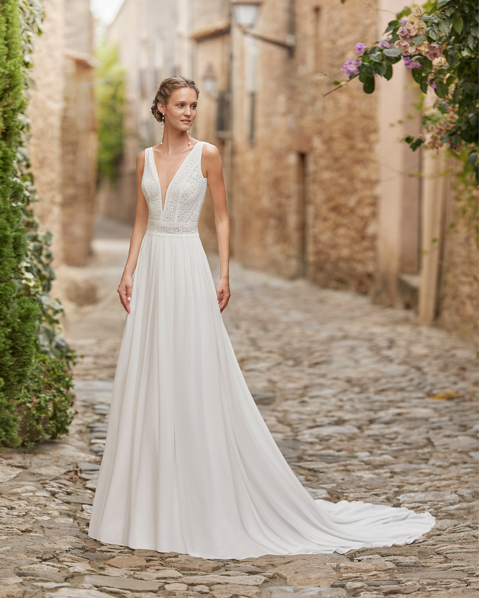 Delicate ballgown-style wedding dress with a lace bodice; with a V-neck, plunging back and pleated skirt. Alma Novia model in georgette. 2022 ALMANOVIA Collection.