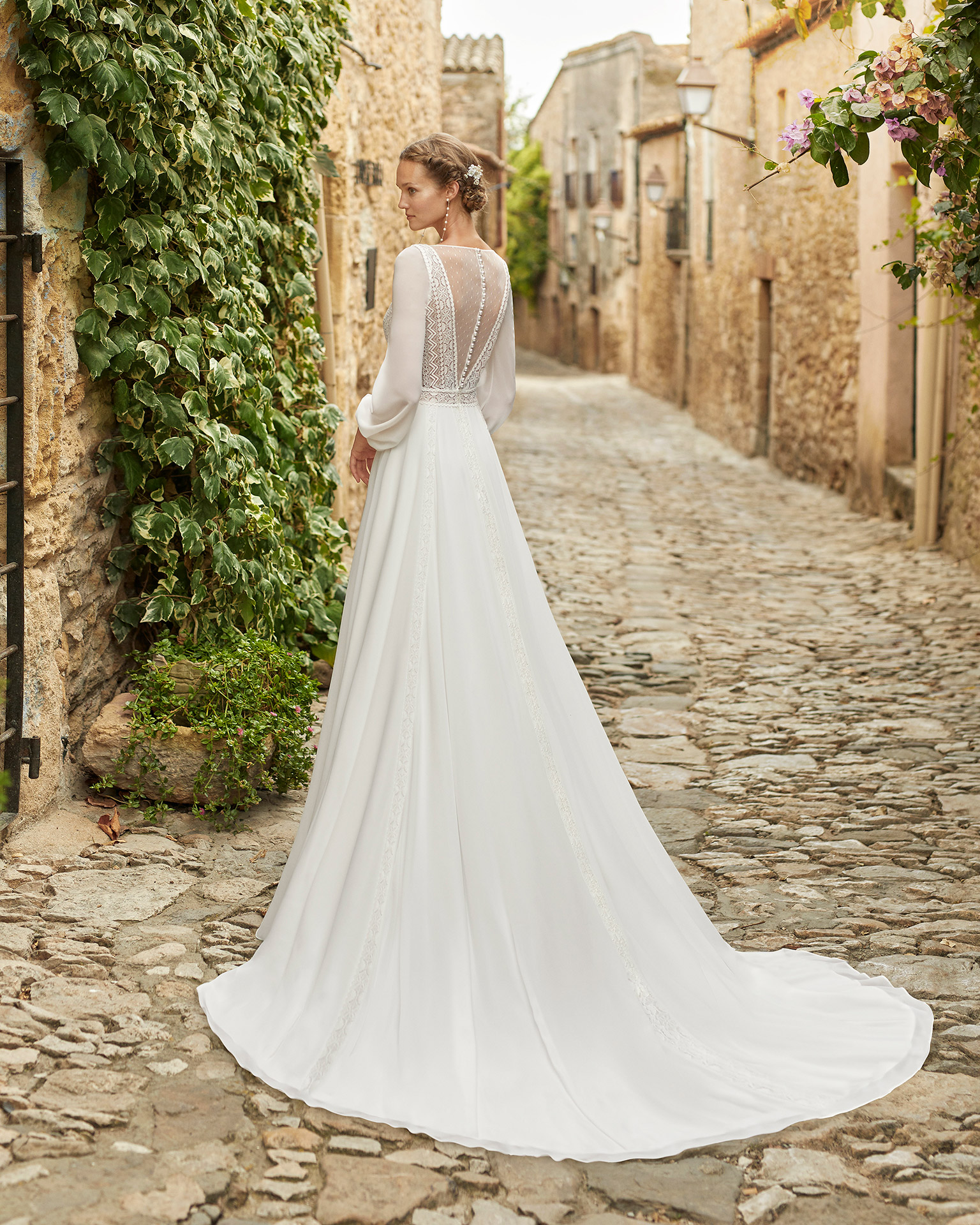 Boho-chic ballgown-style wedding dress with a lace bodice and lace edging applied to the skirt; with a V-neckline, a closed back with dot tulle and pearl buttons, and long georgette sleeves with a lace edging on the cuffs. Alma Novia model in georgette. 2022 ALMANOVIA Collection.