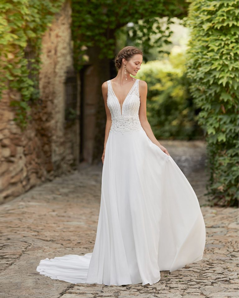 Simple and fluid ballgown-style wedding dress with a beadwork and lace bodice; with a V-neckline and open back. Alma Novia model in georgette. 2022 ALMANOVIA Collection.