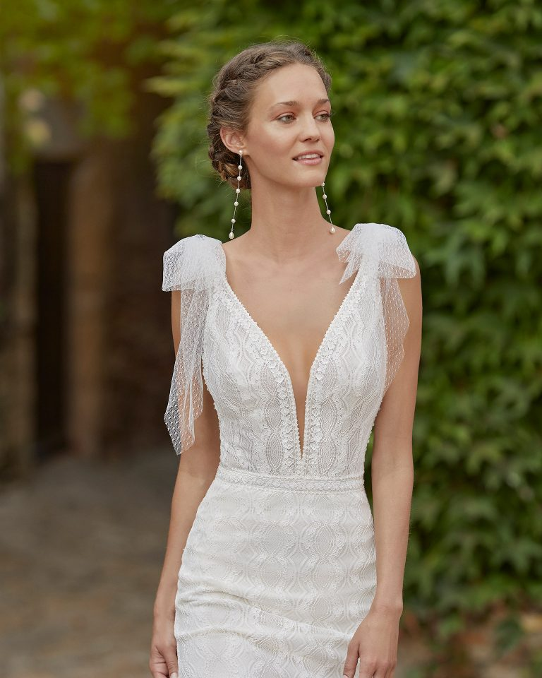 Simple sheath-style wedding dress; with a V-neckline, open back, beadwork details at the waist and slight draped dot tulle on the shoulders. Alma Novia model in lace. 2022 ALMANOVIA Collection.