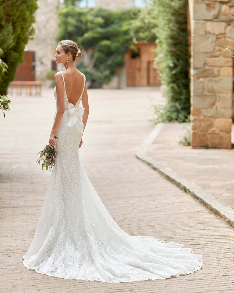 Simple sheath-style wedding dress; with a V-neckline, open back, beadwork details at the waist and neckline, beadwork straps and organdy on the back. Alma Novia model in lace. 2022 ALMANOVIA Collection.