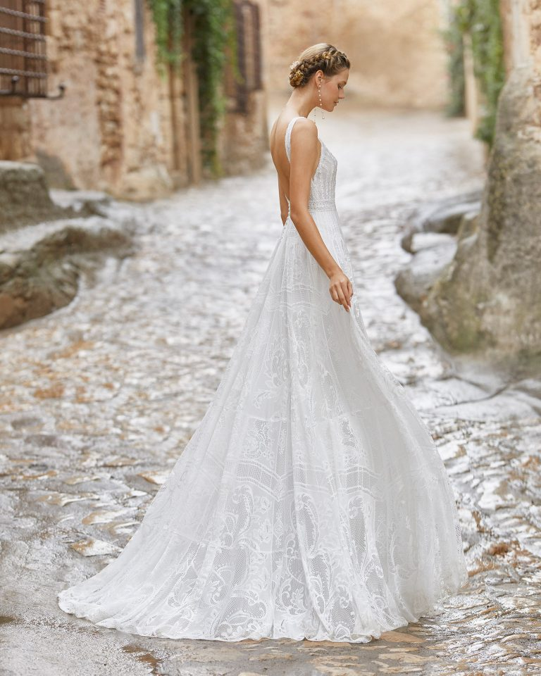 Romantic ballgown-style wedding dress with a beadwork and lace bodice; with a V-neckline, open back, beadwork details at the neckline and sleeves. Alma Novia model in lace. 2022 ALMANOVIA Collection.