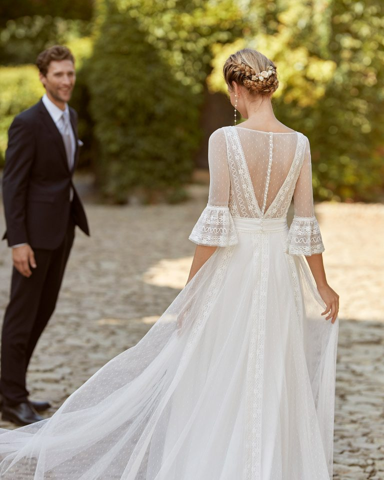 Simple ballgown-style wedding dress; with a V-neckline, a closed back with dot tulle and pearl buttons, three-quarter sleeves with lace on the cuffs and lace edging applied to the skirt. Exclusive Alma Novia model made with crepe and dot tulle. 2022 ALMANOVIA Collection.