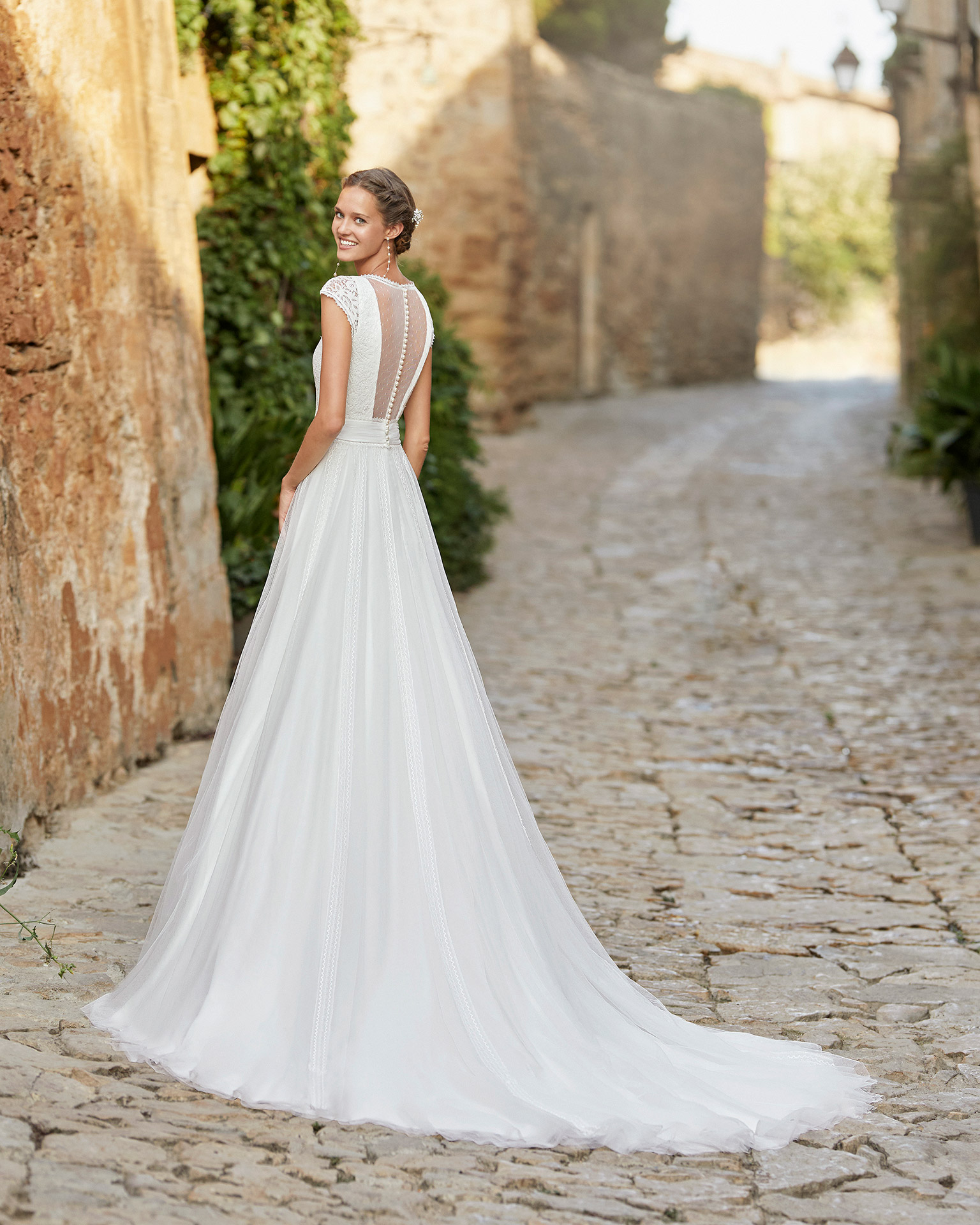 Delicate ballgown-style wedding dress with a lace bodice; with a V-neckline, a closed back with dot tulle and pearl buttons, raglan sleeves with lace and lace edging applied to the tulle skirt. 2022 ALMANOVIA Collection.