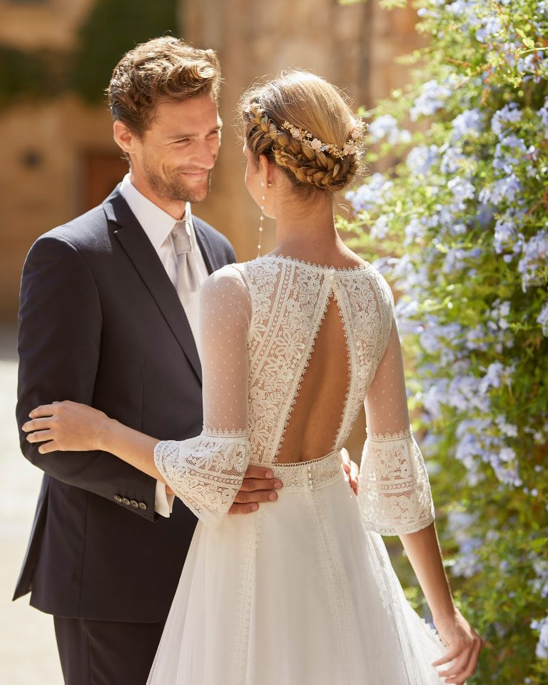 Romantic ballgown-style wedding dress with a lace bodice; a V-neckline, a triangular open back with pearl buttons, three-quarter sleeves and lace edging applied to the skirt. Alma Novia model in dot tulle. 2022 ALMANOVIA Collection.