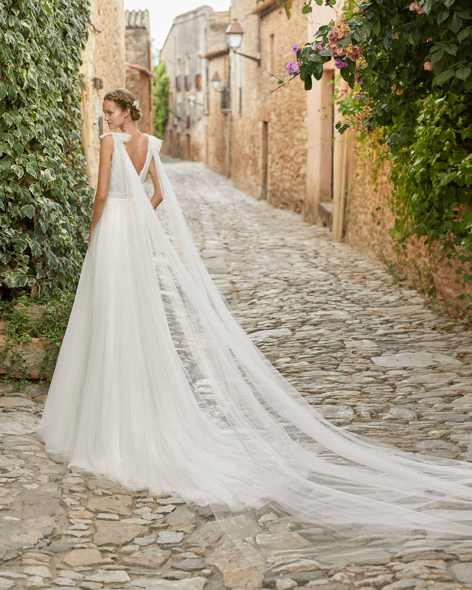 Romantic lightweight ballgown-style wedding dress and long draped tulle; V-neckline, open back and pleated tulle bodice. Alma Novia model in tulle. 2022 ALMANOVIA Collection.