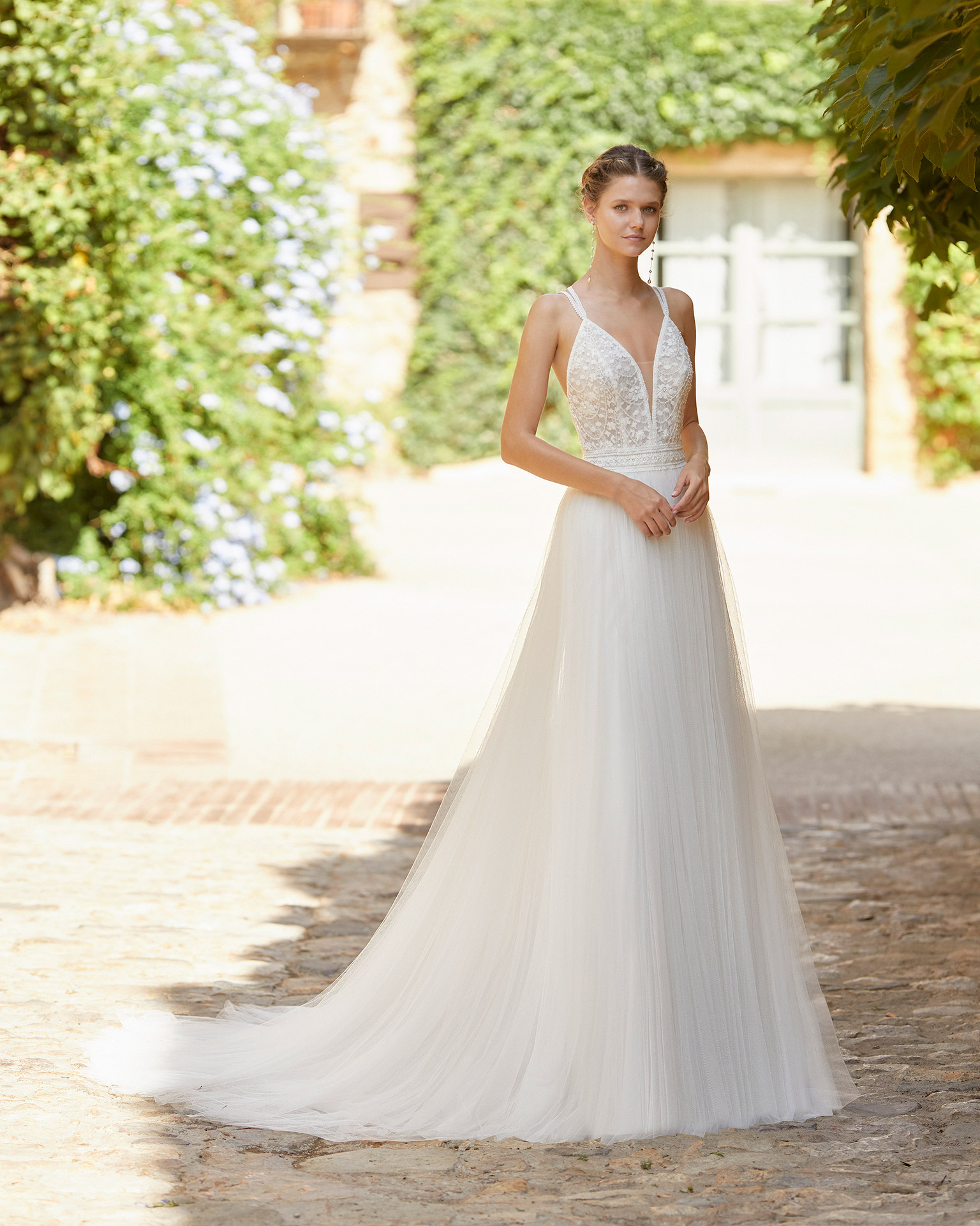 Romantic wedding dress with a lace bodice and beadwork; V-neckline and back with crossed shoulder straps. Alma Novia model in tulle. 2022 ALMANOVIA Collection.