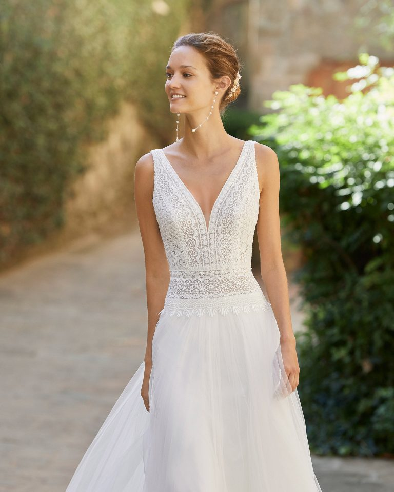 Lightweight sheath-style wedding dress with a lace bodice; V-neckline and open back. Alma Novia model in tulle. 2022 ALMANOVIA Collection.