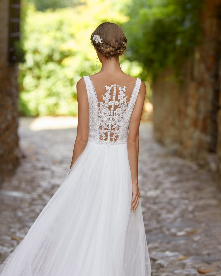 Delicate sheath-style wedding dress with a lace bodice; with a V-neckline, tattoo-effect back, and beadwork details at the waist and neckline. Alma Novia model in tulle. 2022 ALMANOVIA Collection.