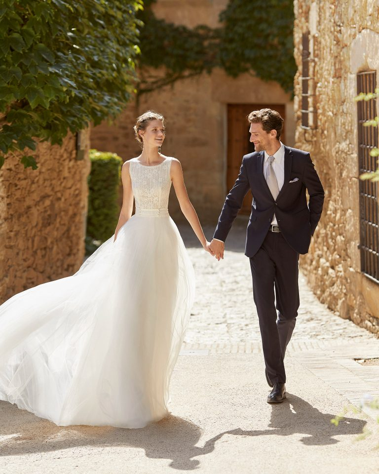Romantic lightweight sheath-style wedding dress with a lace bodice; with a bateau neckline and V-back. Alma Novia model in tulle. 2022 ALMANOVIA Collection.