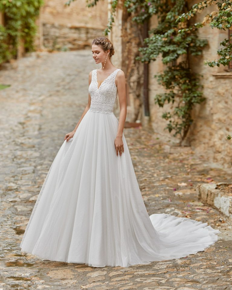 Delicate ballgown-style wedding dress with a lace bodice; V-neckline and plunging back. Alma Novia model in dot tulle. 2022 ALMANOVIA Collection.