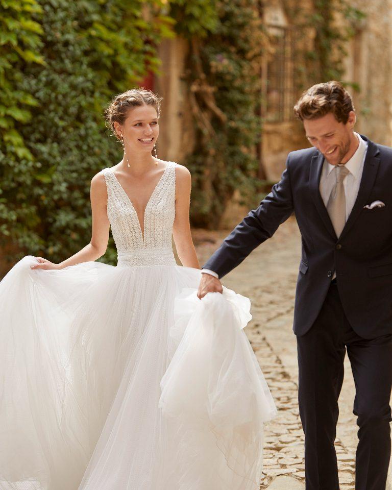 Delicate princess wedding dress with a beadwork and lace bodice; V-neckline and open back. Alma Novia model in dot tulle. 2022 ALMANOVIA Collection.