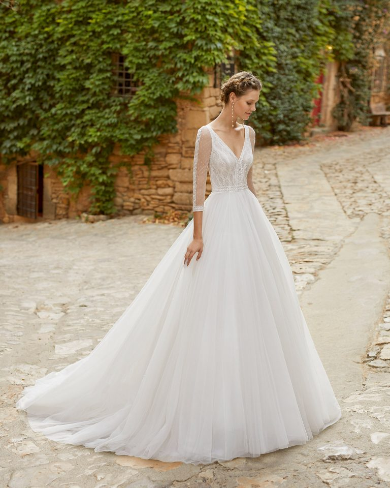 Simple and delicate princess wedding dress with a lace bodice. With a V-neckline, closed back with dot tulle and pearl buttons, and beadwork details at the waist and neckline. Alma Novia model in tulle. 2022 ALMANOVIA Collection.